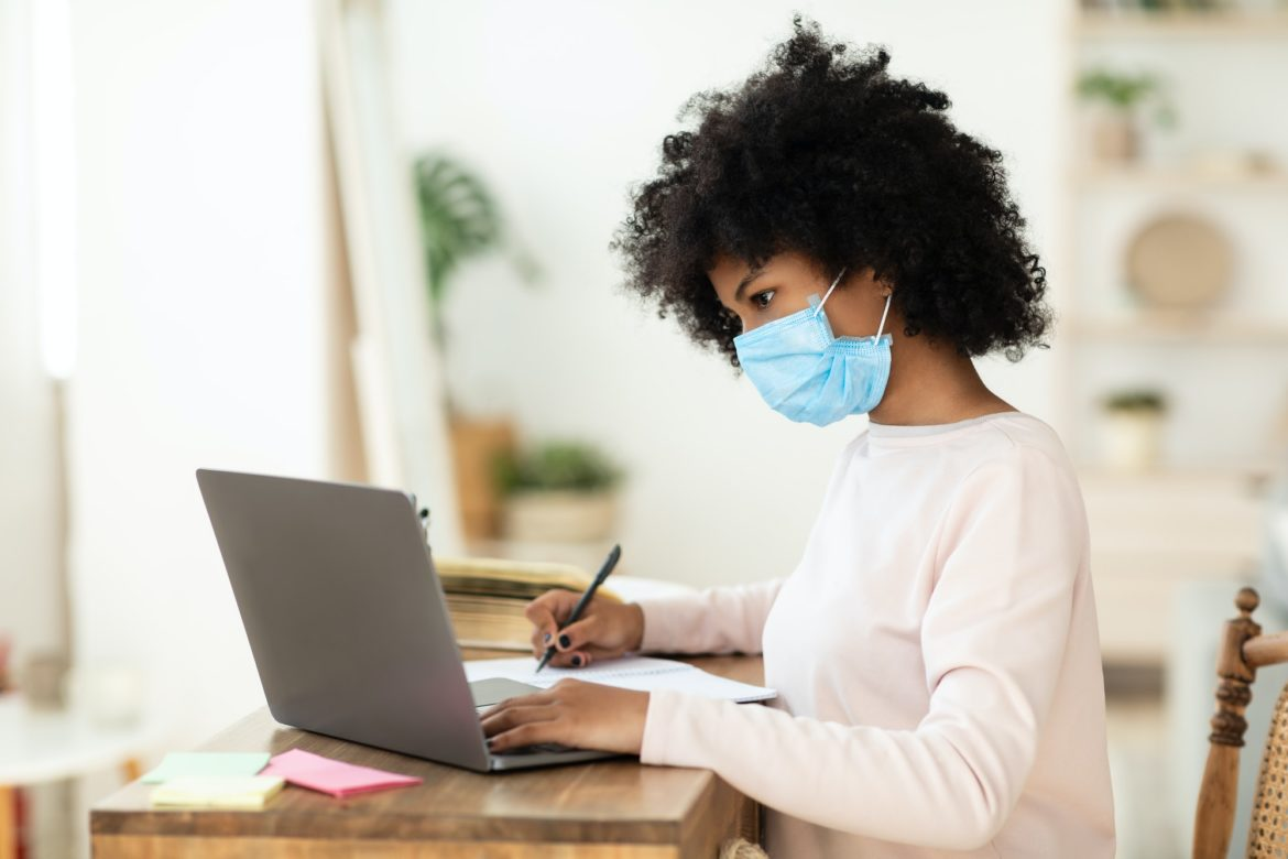 African American Girl In Mask Studying At Laptop At Home